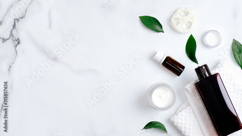 Fototapeta Natural organic cosmetic products and green leaves on marble background. Minimal flat lay style composition with essential oils, shampoo bottle, towel, hand cream. Body care, skincare concept obraz na płótnie