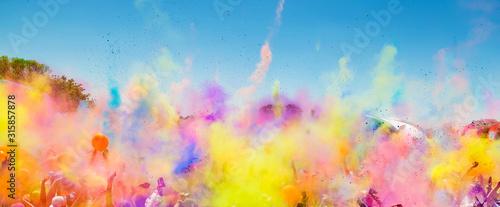 Fototapeta Crowd throwing bright colored powder paint in the air at Holi Festival Dahan obraz