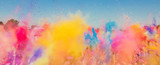 Fototapeta Tęcza - Crowd throwing bright colored powder paint in the air at Holi Festival Dahan