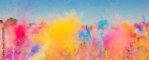 Obraz Crowd throwing bright colored powder paint in the air at Holi Festival Dahan - fototapety do salonu
