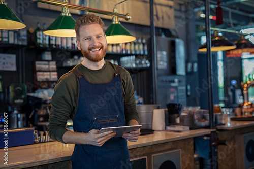 Smiling Waiter ready to take order at pub