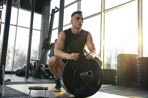 Obraz Confident. Young muscular caucasian athlete training in gym, doing strength exercises, practicing, work on his upper body with weights and barbell. Fitness, wellness, healthy lifestyle concept. - fototapety do salonu