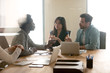Multiracial millennial colleagues discuss ideas at briefing