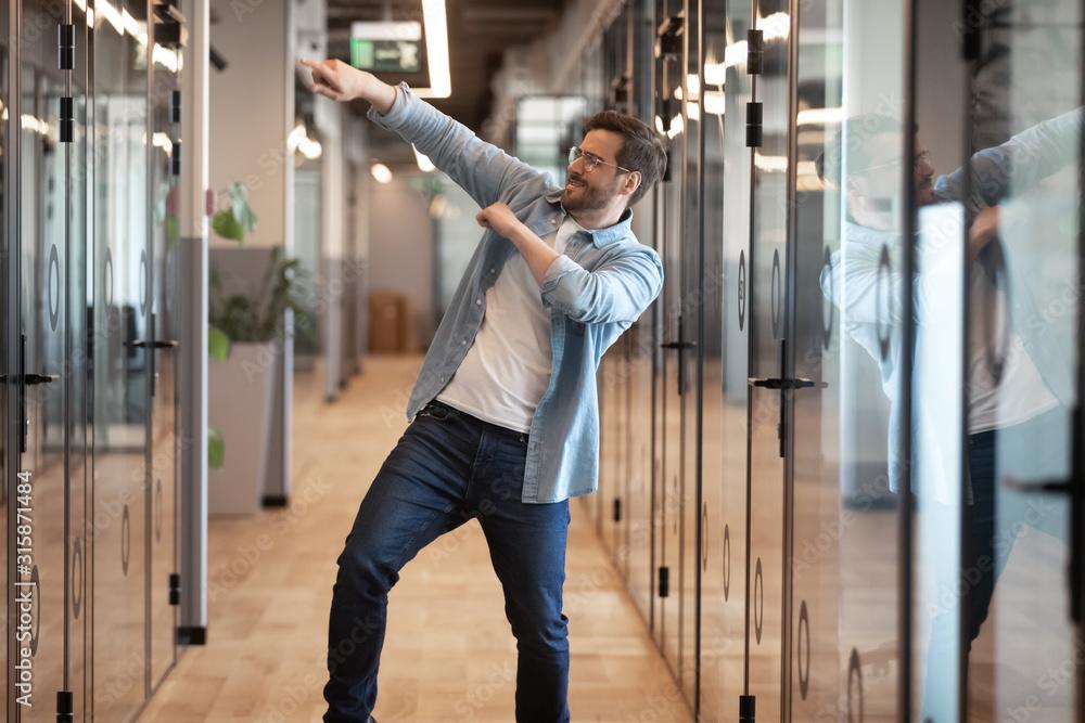 Fototapeta Funny happy male employee dance in office celebrating