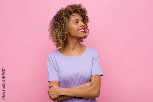 Fototapeta  young african american woman feeling happy, proud and hopeful, wondering or thin