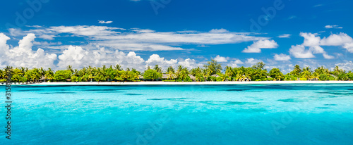 Maldives island panorama. Summer beach landscape, fantastic blue sky palm trees over white sandy beach, villas in luxury resort or hotel. Summer vacation scenery