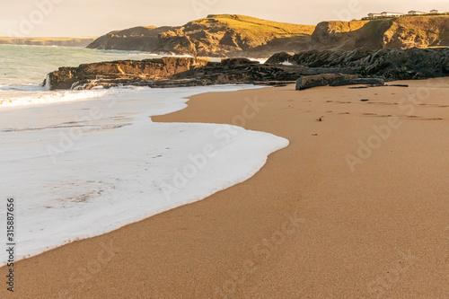 Vászonkép Foam from the receding tide on a deserted Cornish beach
