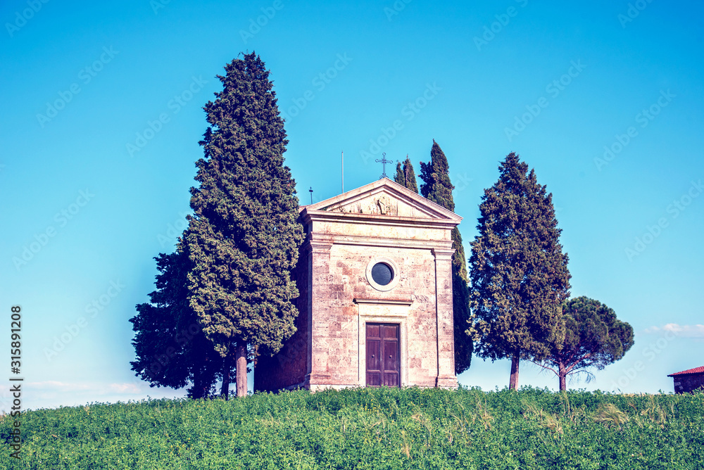 charming landscape with chapel of Madonna di Vitaleta on a sunny day in San Quirico d'Orcia (Val d'Orcia) in Tuscany, Italy. Excellent tourist places.
