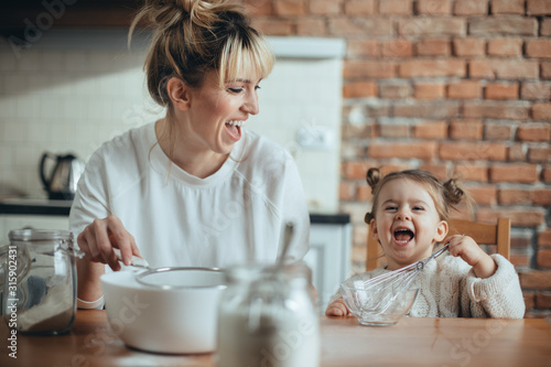 Obraz Mother and daughter baking cookies in their kitchen - fototapety do salonu