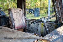 Dirty Old Driver's Seat And Steering Wheel In A Rusty Bus With Broken Windows And With Traces Of Paint In A Forest. Bunker At The Tactical Paintball Playground. Closeup View
