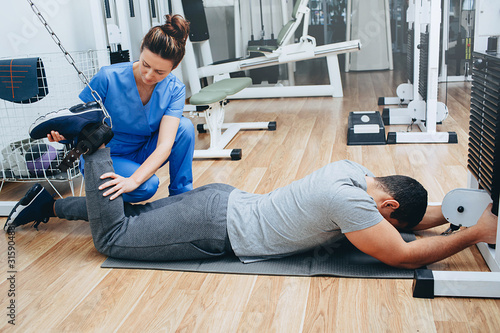 Fotografia Kinesitherapist treats injuries to the athlete's hips after hard training