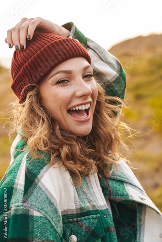 Fotografía Image of young woman wearing hat and plaid shirt walking outdoors