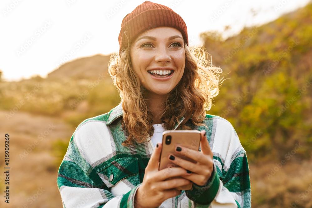Fototapeta Image of joyful young woman holding cellphone while walking outdoors