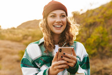 Image Of Joyful Young Woman Holding Cellphone While Walking Outdoors