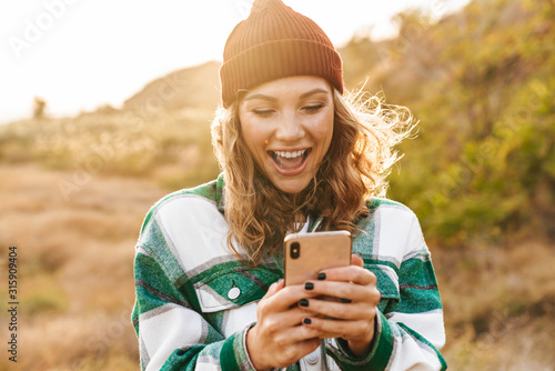 Fototapeta Image of joyful young woman holding cellphone while walking outdoors obraz