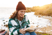 Image Of Joyful Young Caucasian Woman Reading Book By Seaside