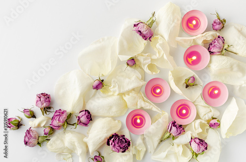 Harmony concept. Burning aroma candles, dried roses and petals on white background. Flat lay, copy space