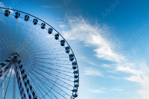 Fotomural  beautiful blue and white ferris wheel among the clouds