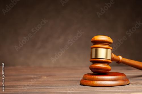 Fotografering Wooden hammer of the judge. Brown background