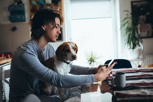 Obraz young man with his dog in kitchen at home, morning scene - fototapety do salonu