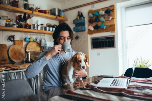 Obraz young man with his dog in kitchen at home, morning scene, - fototapety do salonu