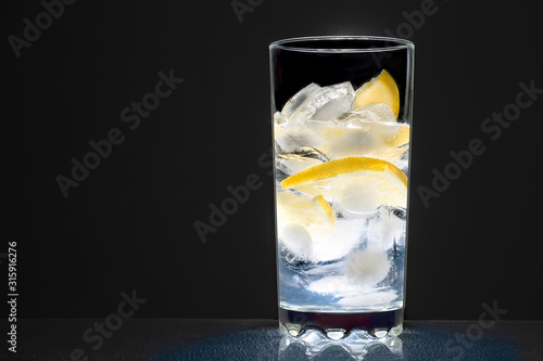 Cuadros en Lienzo  glass cup with water, ice cubes and lemon on a dark background