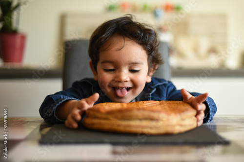 Leinwand Poster young boy happy to eat kings cake
