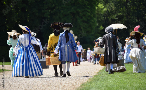 Photo Unidentified people costumed in the fashions of the 17th french aristocracy, walking in French formal gardens