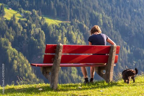 Obraz young woman sitting on a bench mountain view - fototapety do salonu