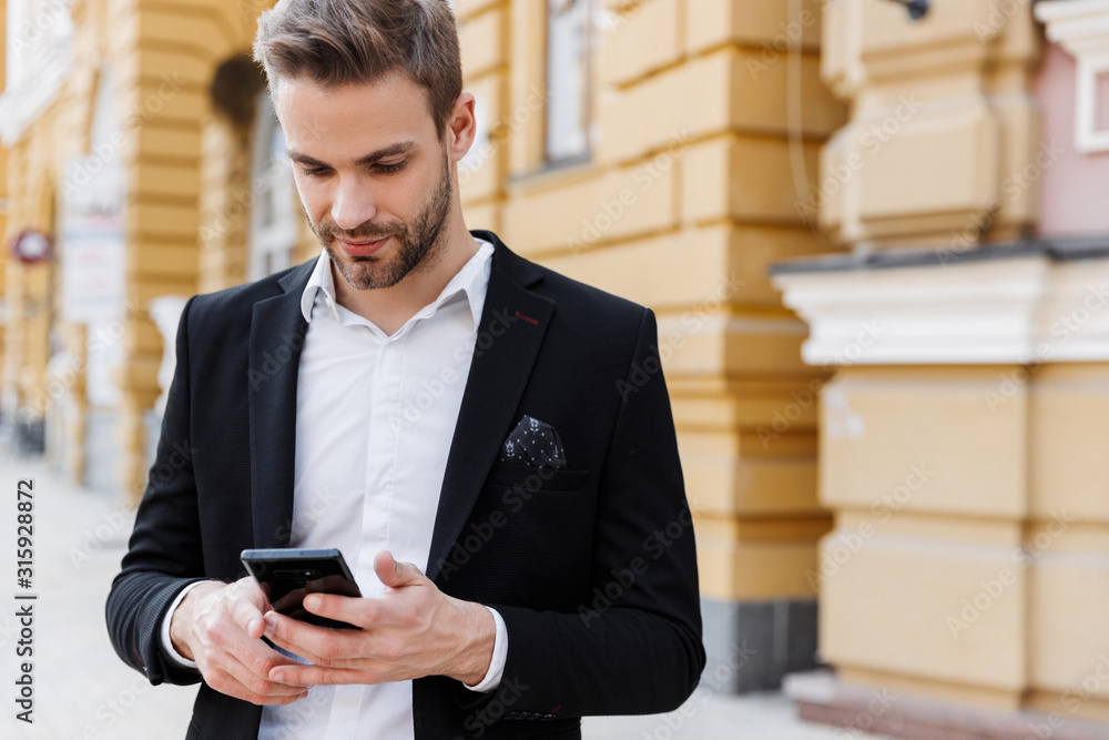 Fototapeta Charming young businessman wearing suit standing at the city