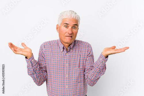 Photo Senior caucasian man isolated confused and doubtful shrugging shoulders to hold a copy space