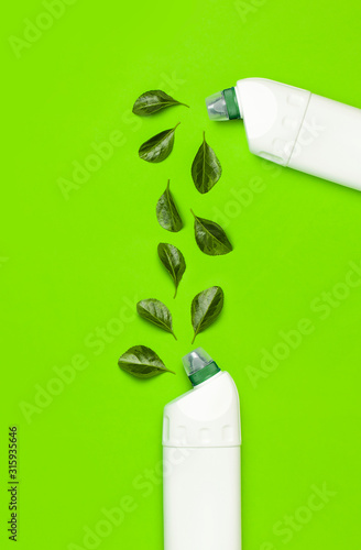 White plastic bottle for liquid detergent, cleaning agent, bleach, antibacterial gel with natural plant extract and green leaves on green background. Eco style cleaning concept. Flat lay top view
