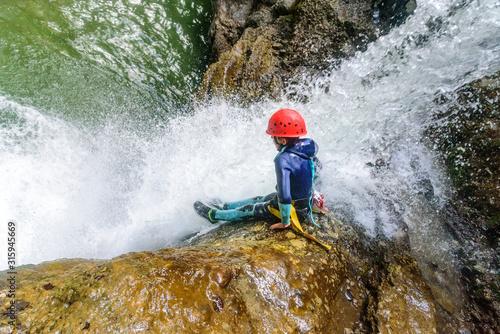 Mutprobe beim Canyoning - Felsrutsche in einen Wasserfall Canvas Print