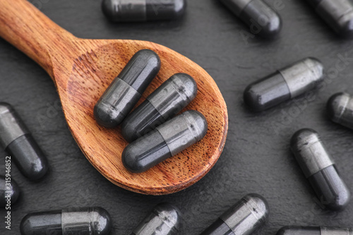 Fotografia Activated vegetable charcoal capsules in a wooden spoon