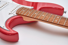 Fragment Of A Red Electric Guitar On A White Background. Part Of The Guitar. Music Object.