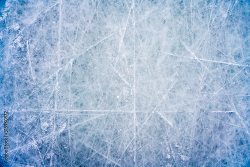 Photo Ice background with marks from skating and hockey, blue texture of rink surface