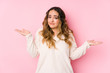 Young curvy woman posing in a pink background isolated doubting and shrugging shoulders in questioning gesture.