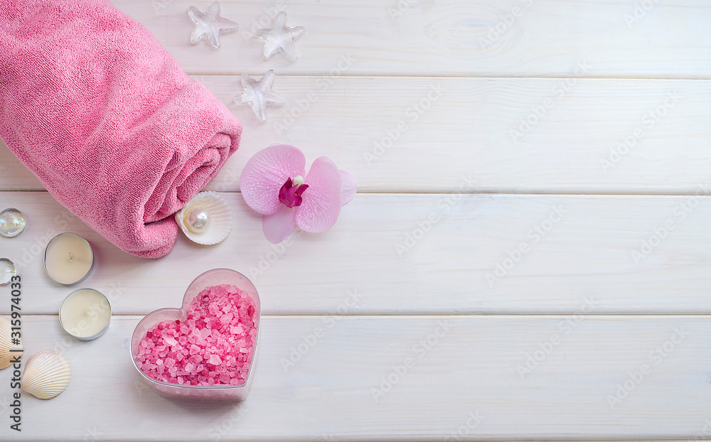 Fototapeta Spa treatments as a gift for Valentine's Day. Pink towel with a flower, shells and pink sea salt in the form of a heart on a white wooden background. Beauty salon
