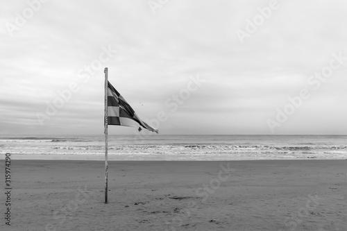Fototapeta Waving old flag on the empty beach. Black and white photo obraz na płótnie