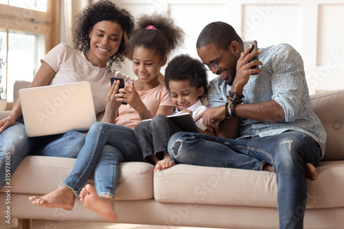 Happy addicted to gadgets black family using different devices. Wallpaper Mural