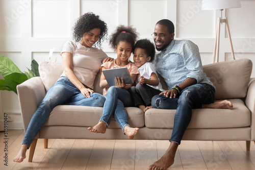 Happy african american family using tablet together.