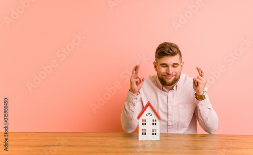 Young caucasian man sitting with a house icon crossing fingers for having luck Tableau sur Toile