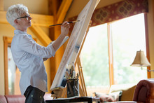 Middle-aged Woman Painting On Canvas In Her Cottage