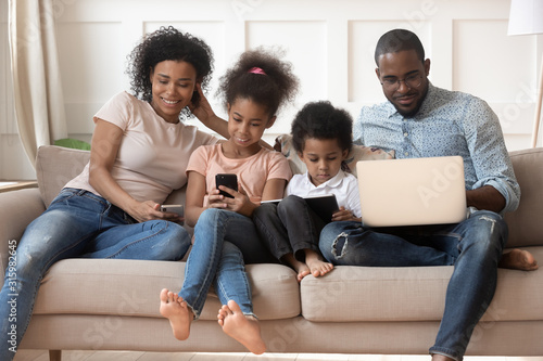 Happy black family addicted to internet technology. Wallpaper Mural