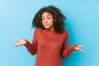 canvas print picture - Young african american curly hair woman doubting and shrugging shoulders in questioning gesture.
