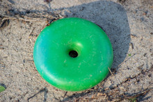 Abandoned Toys - A Childs Green Disk Toy Found As Trash Along A Path