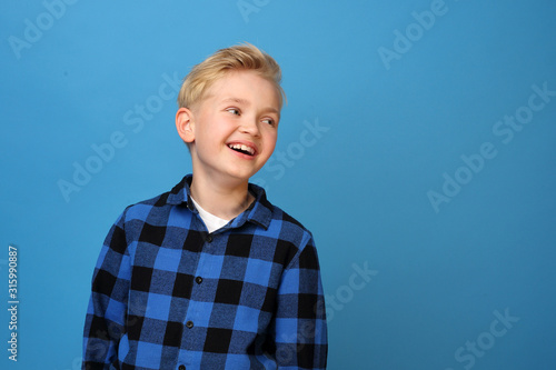 Obraz Smiling boy, happy child.  Happy, smiling boy on a blue background expresses emotions through gestures. - fototapety do salonu