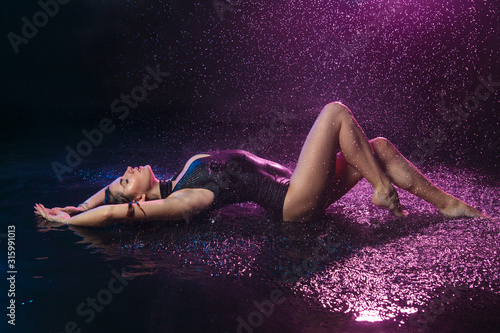 Obraz na plátně A beautiful sexy girl in a swimsuit lies on her back under the drops of falling water with purple backlight on a black background