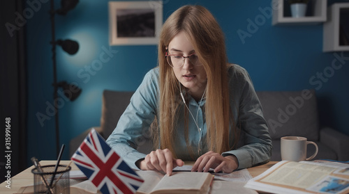 Obraz na plátně  Serious woman studying English following line with her finger while reading, sit