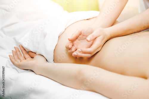 Young beautiful woman having professional back massage in spa salon